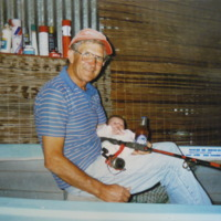 Colin Schultz, father of Tracy Bye, sitting in his famous fishing boat with her daughter Lucy, [no date]