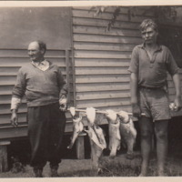 Two men pictured holding four fish, [n.d.]
